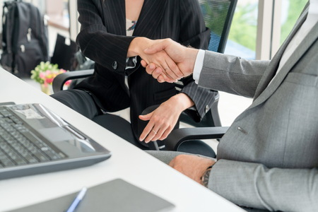 Businessman executive handshake with businesswoman worker in modern workplace office. People corporate business deals concept.