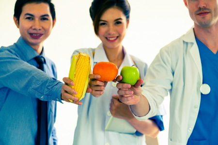 Group of nutritionists presenting diet food of fruit and vegetables for cholesterol control showing awareness and prevention of heart disease. Healthy eating and good nutrition concept. 写真素材