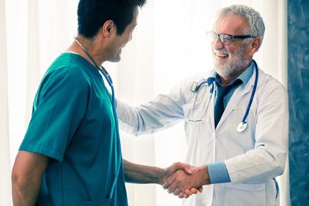 Médico de sexo masculino mayor que trabaja con otro médico en el hospital. Concepto de salud médica y educación del personal médico.