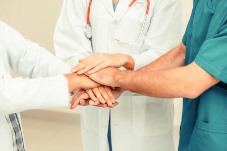 Medical service teamwork - Doctor, surgeon and nurse join hands together.