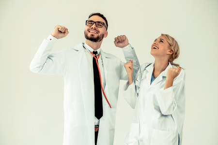 Happy successful doctor celebrates victory in hospital office with another doctor standing beside her for the success of patient treatment.