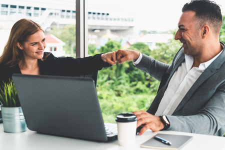 Success business partner - Businesswoman and businessman celebrating together in modern workplace office. People corporate teamwork concept. Stock Photo