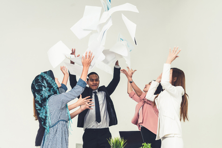 Smiling business people having fun by throwing papers in the air celebrating business success in the modern office. Happy workplace and casual career company concept. Imagens