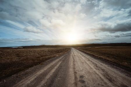 Strada sterrata di ghiaia vuota attraverso il paesaggio di campagna e il campo in erba. Viaggio natura off road per veicolo a quattro ruote motrici. Archivio Fotografico
