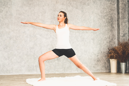 Young beautiful woman do yoga exercise on carpet at home living room. Healthy lifestyle and relaxation. Stok Fotoğraf