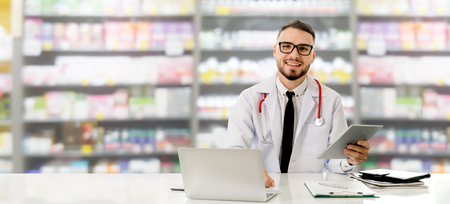Pharmacist using tablet computer at the pharmacy. Medical healthcare and pharmaceutical staff service. Stockfoto