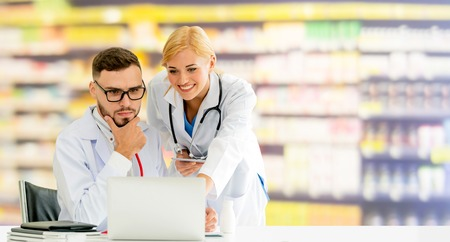 Doctor working with laptop computer at the office while having discussion with another doctor in the hospital. Medical healthcare and doctor service.