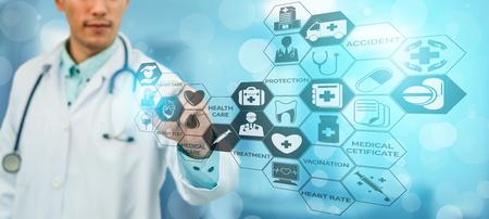 Medical Healthcare Concept - Doctor in hospital with digital medical icons graphic banner showing symbol of medicine, medical care people, emergency service network, doctor data of patient health. Reklamní fotografie - 124824438