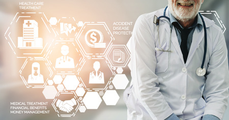 Health Insurance Concept - Doctor in hospital with health insurance related icon graphic interface showing healthcare people, money planning, risk management, medical treatment and coverage benefit. Stock Photo