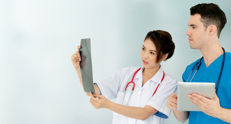 Female doctor looking at x ray film while discussing with another doctor holding a tablet computer at the hospital. Medical healthcare staff and doctor service.
