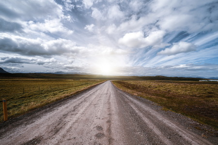 Empty gravel dirt road through countryside landscape and grass field. Nature off road travel trip for four-wheel-drive vehicle. Stock Photo