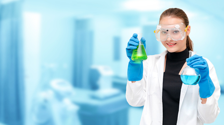 Portrait of young happy scientist or chemist holding test tube in laboratory. Chemical or medical technology research and development concept. Stok Fotoğraf