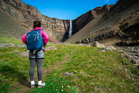 Woman traveler trekking in Icelandic summer landscape at the Hengifoss waterfall in Iceland. The waterfall is situated in the eastern part of Iceland.