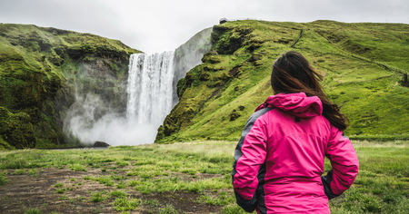 Woman traveler at beautiful scenery of the majestic Skogafoss Waterfall in countryside of Iceland in summer. Skogafoss is the top famous natural landmark and tourist attraction of Iceland and Europe. Reklamní fotografie