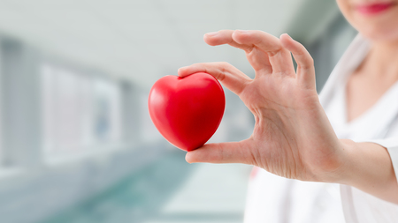 Doctor holding a red heart at hospital office. Medical health care and doctor staff service concept. Banco de Imagens
