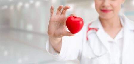 Doctor holding a red heart at hospital office. Medical health care and doctor staff service concept. Фото со стока