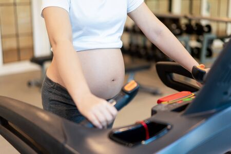 Active pregnant woman exercise in fitness center at yoga room. The young expecting mother holding baby in pregnant belly. Maternity prenatal care and woman pregnancy concept.