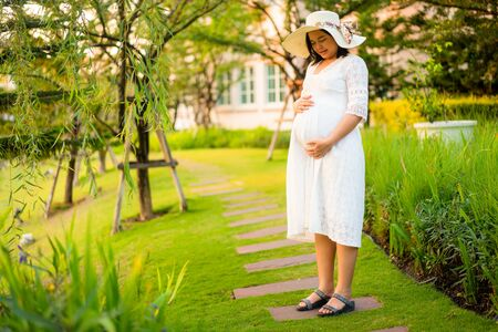 Pregnant woman feeling happy with new life at garden home while take care of her child. The young expecting mother holding baby in pregnant belly. Maternity prenatal care and woman pregnancy concept.