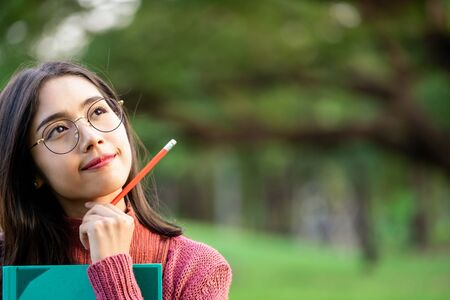 Young creative student girl thinking or planning future education while holding pencil in hand. Creativity idea and learning concept. Reklamní fotografie