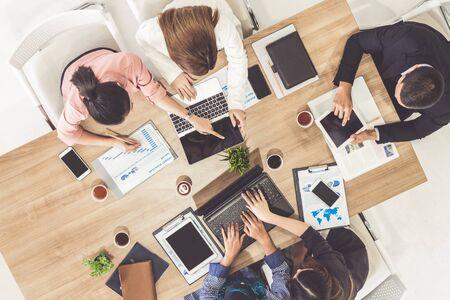 Draufsicht des Geschäftsmannes in Gruppentreffen mit anderen Geschäftsleuten und Geschäftsfrauen im modernen Büro mit Laptop-Computer, Kaffee und Dokument auf dem Tisch. Menschen Corporate Business-Team-Konzept.