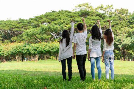 Jeunes étudiants heureux d'hommes et de femmes levant la main pour célébrer et montrer le travail d'équipe dans le parc de l'école ou de l'université. Concept de charité, de bénévolat et d'unité.