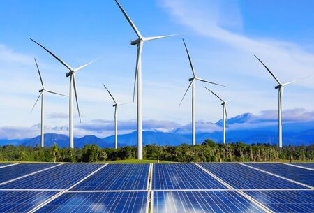 Solar energy panel photovoltaic cell and wind turbine farm power generator in nature landscape for production of renewable green energy is friendly industry. Clean sustainable development concept. Stock Photo
