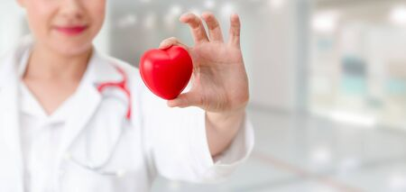 Doctor holding a red heart at hospital office. Medical health care and doctor staff service concept. Archivio Fotografico