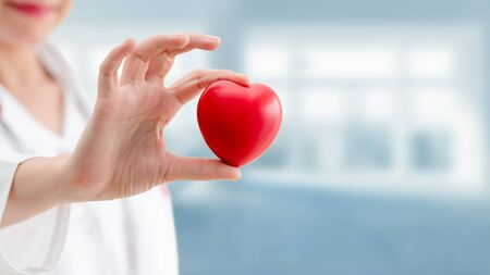Doctor holding a red heart at hospital office. Medical health care and doctor staff service concept. Imagens