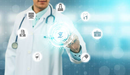 Medical Healthcare Concept - Doctor in hospital with digital medical icons graphic banner showing symbol of medicine, medical care people, emergency service network, doctor data of patient health. Foto de archivo