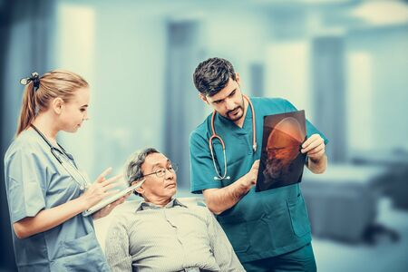 Surgeon showing xray film to senior patient looking at brain injuries with nurse standing beside the surgeon at the hospital room. Medical healthcare and surgical doctor service concept.