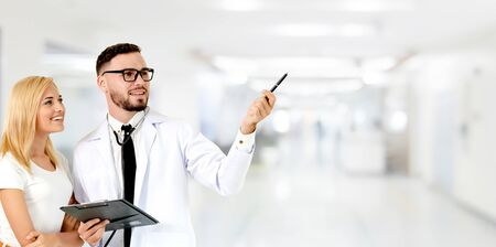 Doctor with patient pointing at empty copy space for your text. The happy patient is listening to explanation from the doctor. Concept of medical healthcare and doctor staff service.