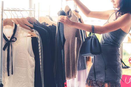 Mooie vrouw winkelen voor kleding bij kledingwinkel in het winkelcentrum. Moderne handelslevensstijl.