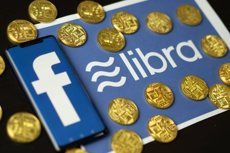 Bangkok, Thailand - July 2, 2019: Phone with Facebook logo on screen is placed on paper with Libra logo. Facebook reported to utilize new cryptocurrency called Libra expected to be used on Facebook. 에디토리얼