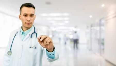 Doctor pointing pen at empty copy space for your text. Healthcare and medical service. Imagens