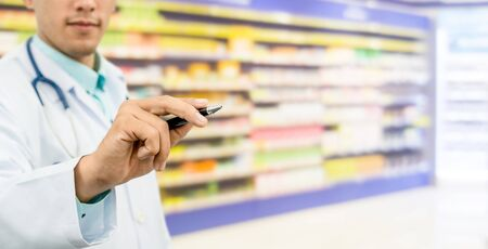 Pharmacist in pharmacy pointing pen at empty copy space for your text. Healthcare and pharmaceutical service.
