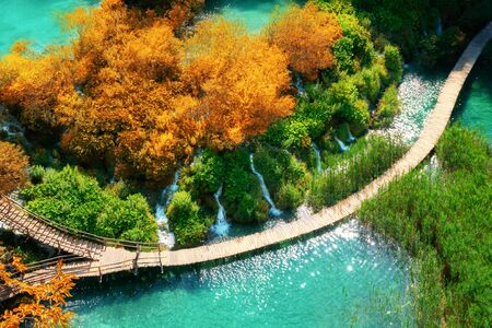 Beautiful wooden path trail for nature trekking with lakes and waterfall landscape in Plitvice Lakes National Park, famous travel destination of Croatia.