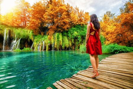 Woman traveler walking on wooden path trail with lakes and waterfall landscape in Plitvice Lakes National Park, famous travel destination of Croatia. Stockfoto