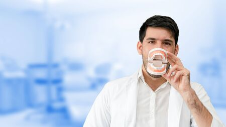 Young male dentist showing toothbrush and denture in dental clinic. Selective focus at the toothbrush. Stockfoto