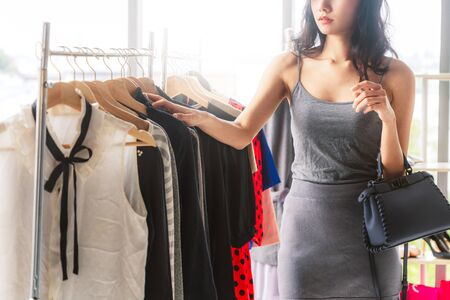 Beautiful woman shopping for clothes at retail apparel shop in the shopping mall. Modern trade lifestyle. Stock fotó