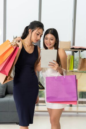 Two Asian women shopping at retail shop in the shopping mall. Modern trade lifestyle. Stock Photo