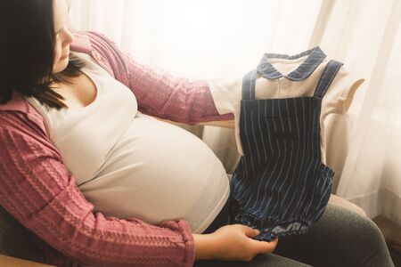 Pregnant woman feeling happy at home while taking care of her child. The young expecting mother holding baby in pregnant belly. Maternity prenatal care and woman pregnancy concept. Stok Fotoğraf