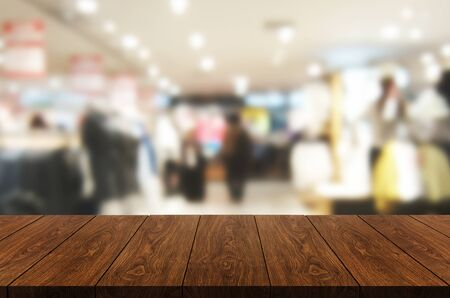 Wood table in shopping mall or department store blur background with empty copy space on the table for product display mockup. Modern trade and retail goods shopping concept.