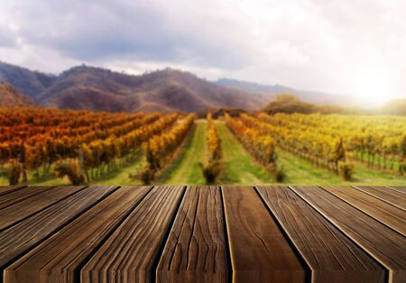 Brown wood table in autumn vineyard landscape with empty copy space on the table for product display mockup. Winery and wine tasting concept. Stok Fotoğraf
