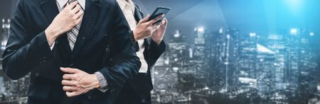 Double Exposure Image of Business Communication Network Technology Concept - Business people using smartphone or mobile phone device on modern cityscape background. Stockfoto