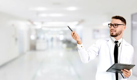 Young male doctor pointing at empty copy space for your text in the hospital. Medical healthcare and doctor staff service.