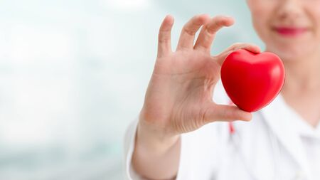 Doctor holding a red heart at hospital office. Medical health care and doctor staff service concept. Zdjęcie Seryjne