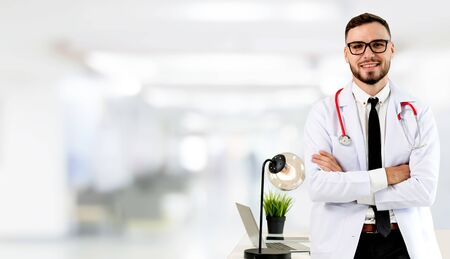 Handsome doctor standing in hospital office and looking at camera. Medical healthcare and doctor staff service.