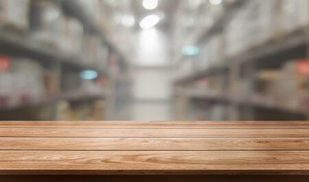 Holztisch im Lagerhaus verwischt Hintergrund mit leerem Kopienraum auf dem Tisch für Produktanzeigemodell. Hardware-Warenverteilung und industrielles Logistikkonzept. Standard-Bild