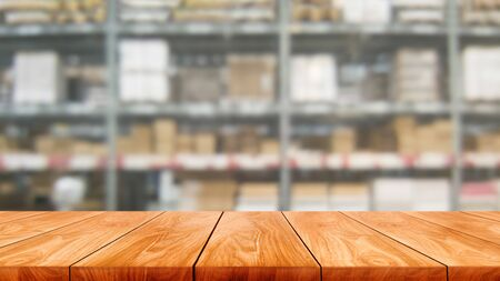 Holztisch im Lagerhaus verwischt Hintergrund mit leerem Kopienraum auf dem Tisch für Produktanzeigemodell. Hardware-Warenverteilung und industrielles Logistikkonzept.
