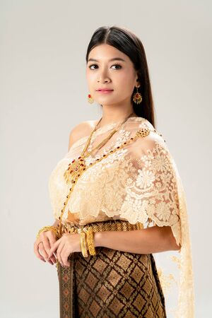 Beautiful Thai woman portrait dress up in traditional thai costume on white background. Thailand culture concept.